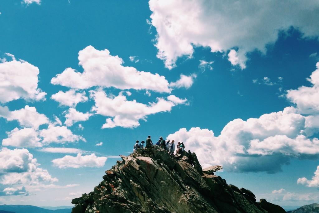 people on a mountain blue sky