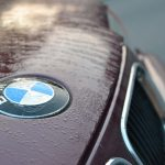 shot of BMW emblem in rain on car